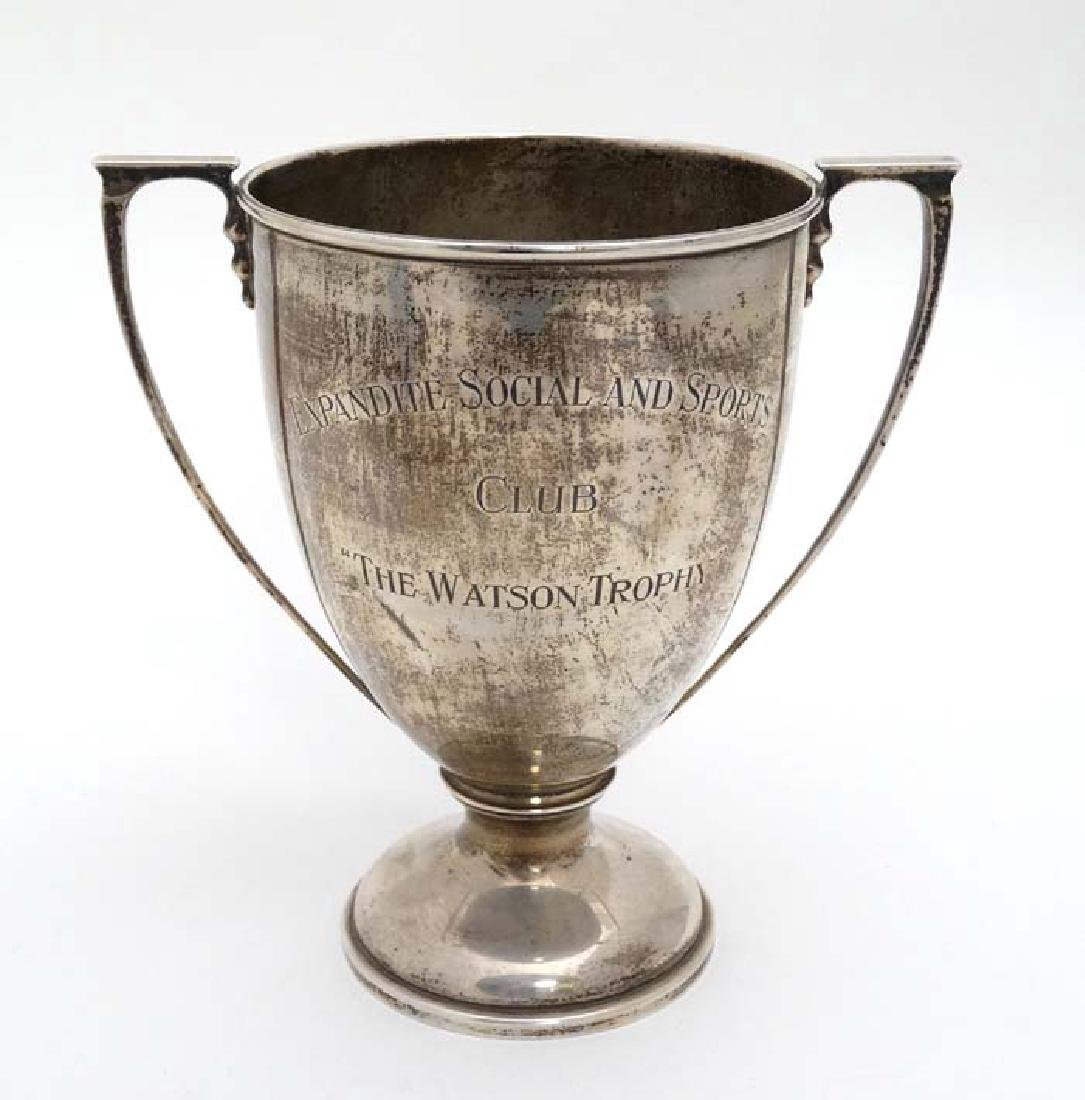 A silver trophy cup with two handles and engraved '
