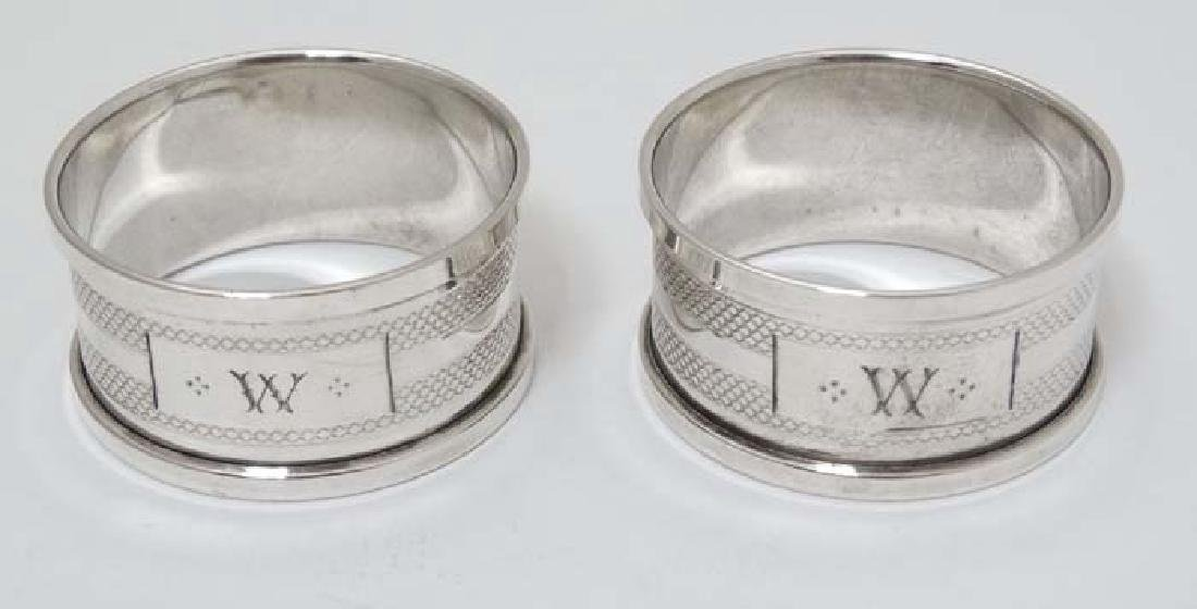 A pair of silver napkin rings with engine turned