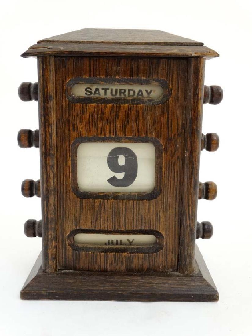 A c.1900 oak desk calendar having day, date and month