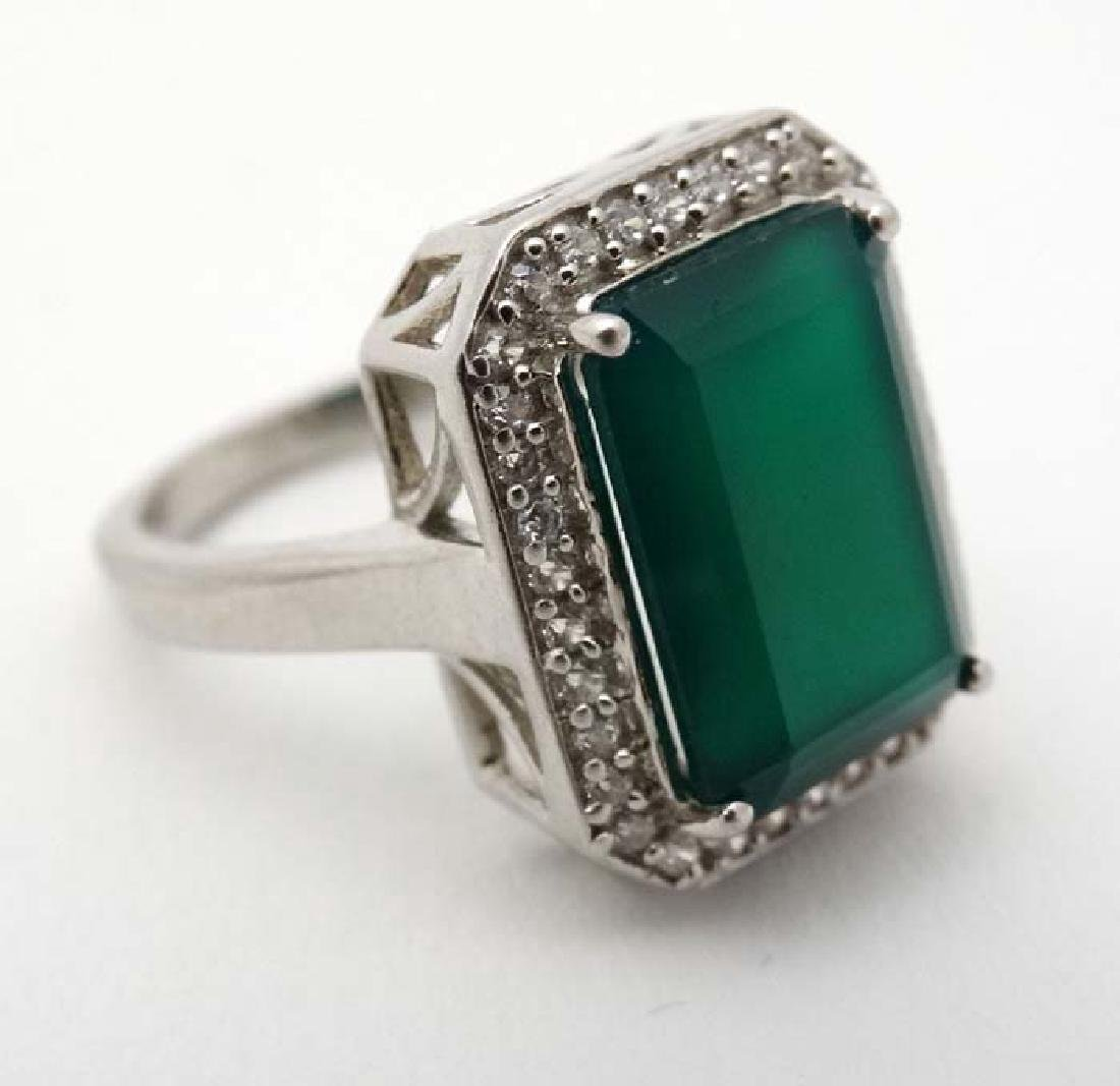 A silver ring set with green stone bordered by white