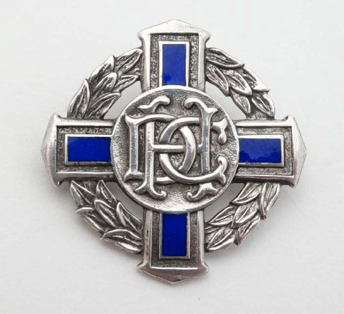A hallmarked silver brooch of cross and laurel chaplet