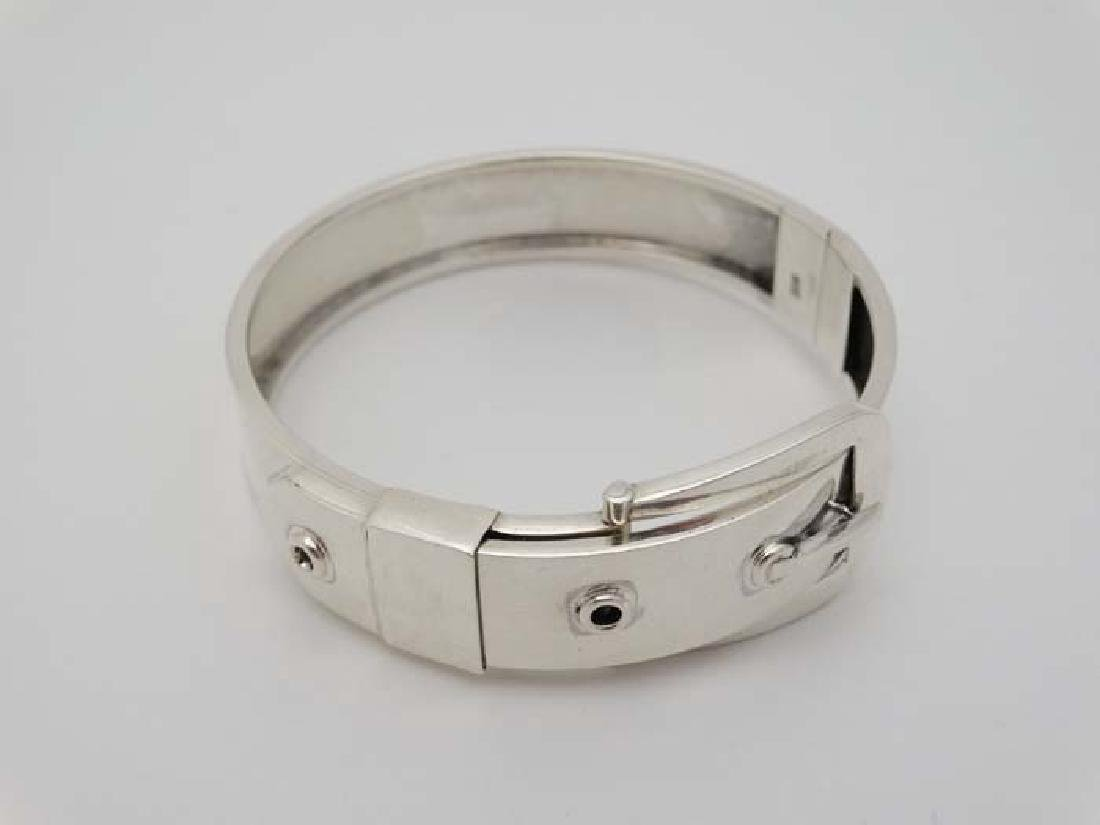 A silver bangle bracelet formed as a belt with buckle