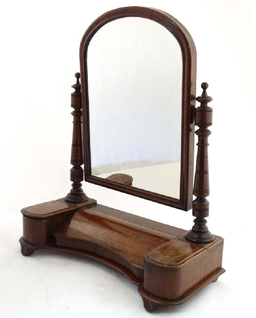 A Victorian dressing table mirror with arch shaped