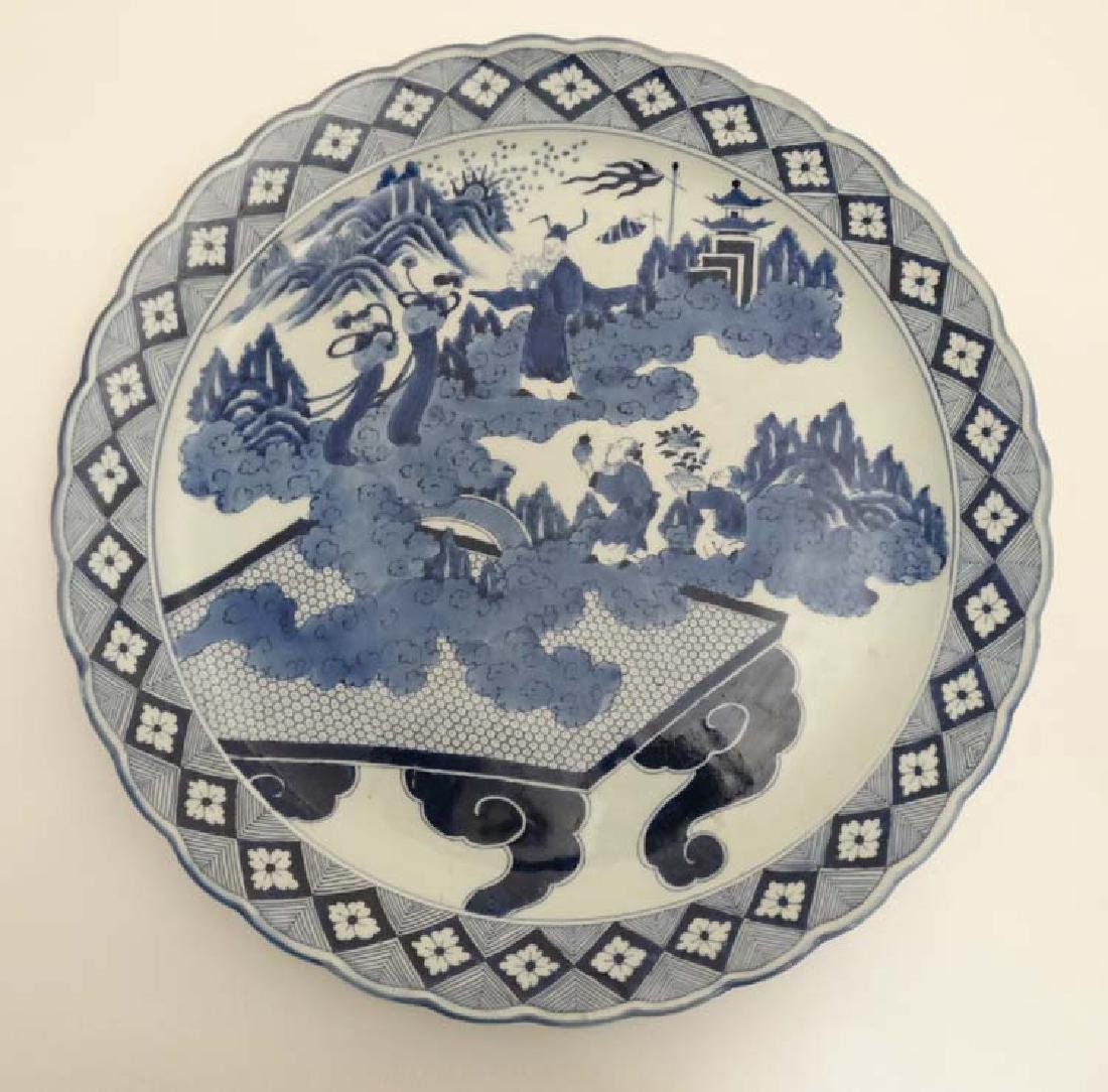 A large blue and white Japanese charger decorated with