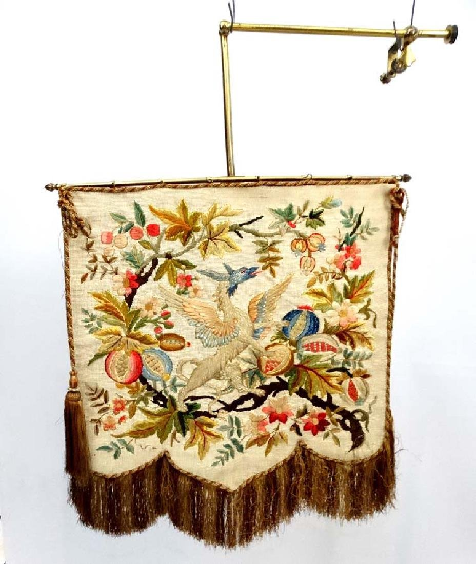 A Victorian brass hinged banner screen with crewelwork