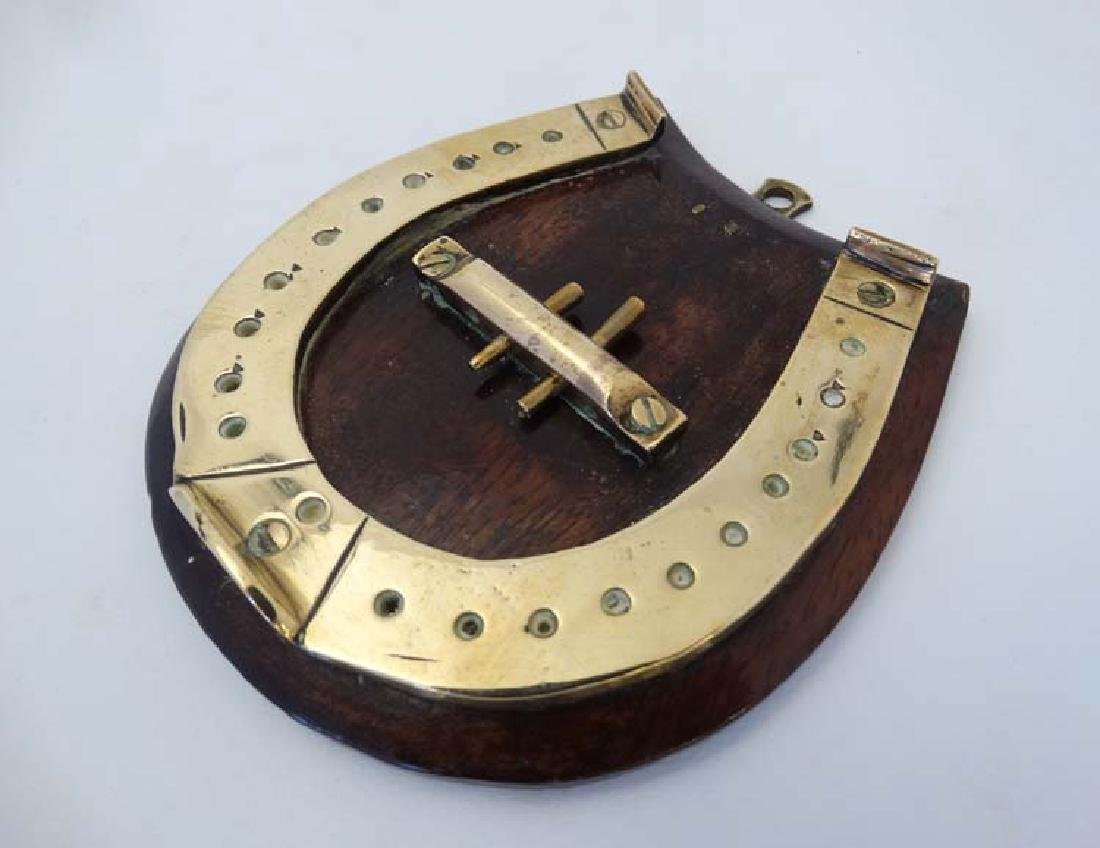 A small brass cribbage board formed as a horseshoe,