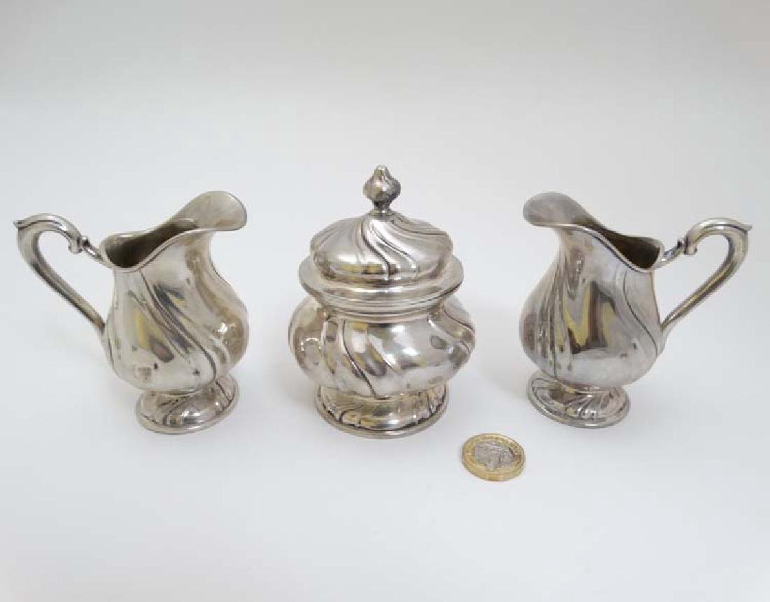 A pair of German .800 silver cream jugs together with a