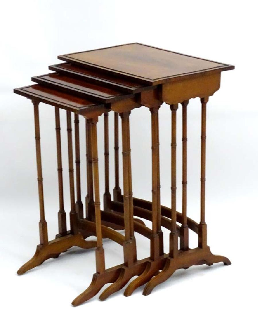 An early 20thC mahogany nest of four tables with inlay