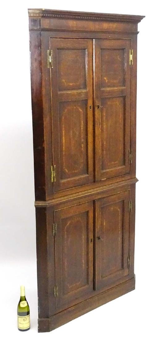 A late 18thC oak floor standing Corner Cupboard with