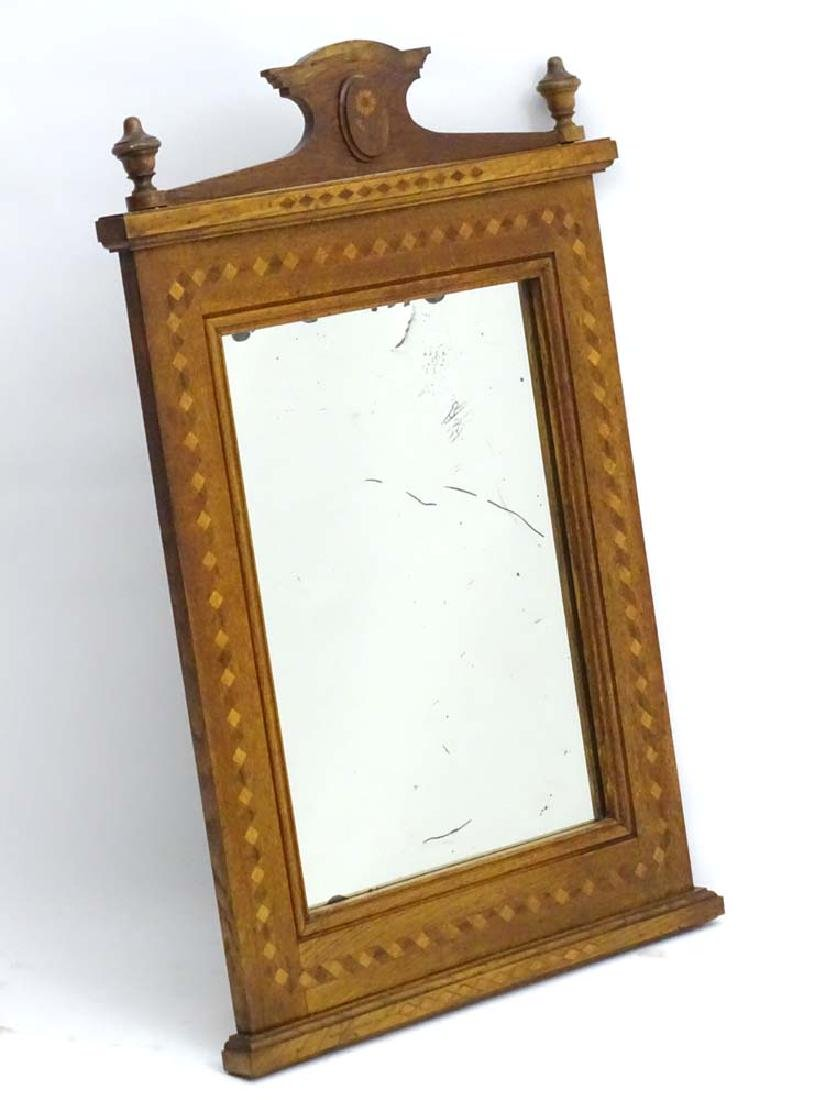 An early 20thC Oak Mirror with shaped pediment having