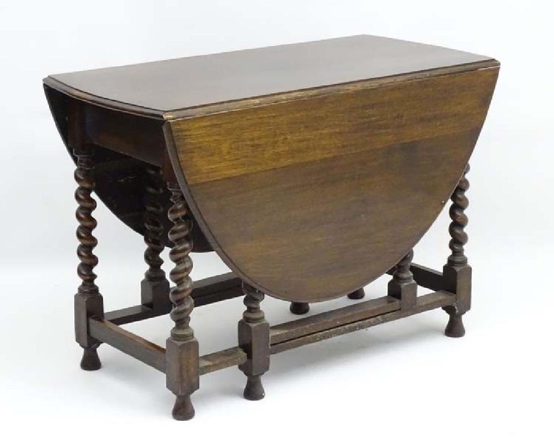 An early 20thC oak oval Gate leg Table with barley