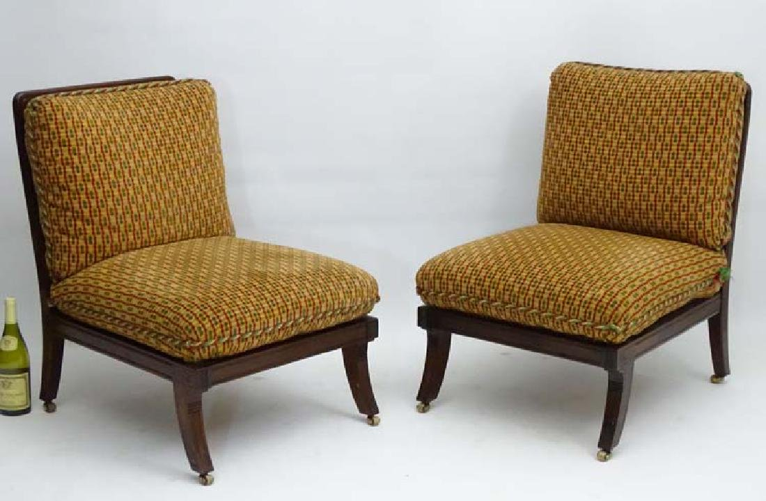 A pair of Regency style Lounge Chairs standing on sabre