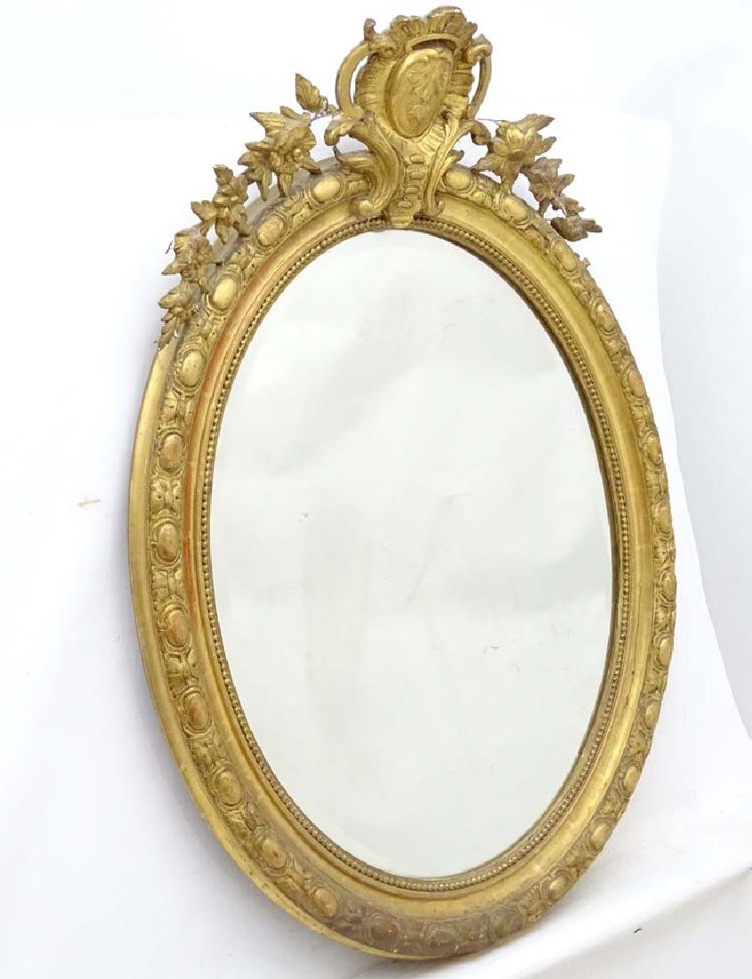 A 19thC French gilt oval mirror with floral carving