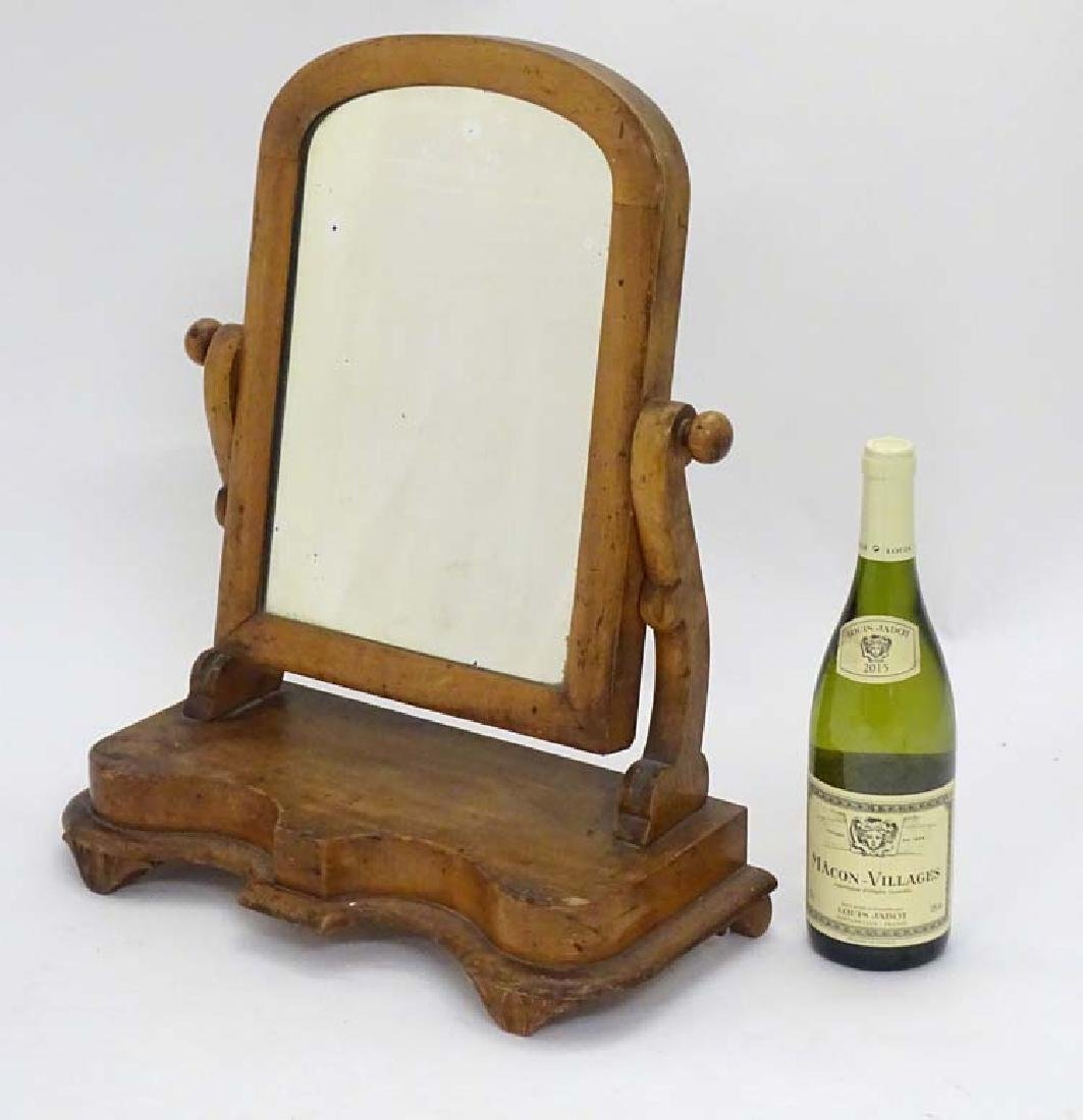 A Victorian walnut oval Toilet Mirror on cupids bow