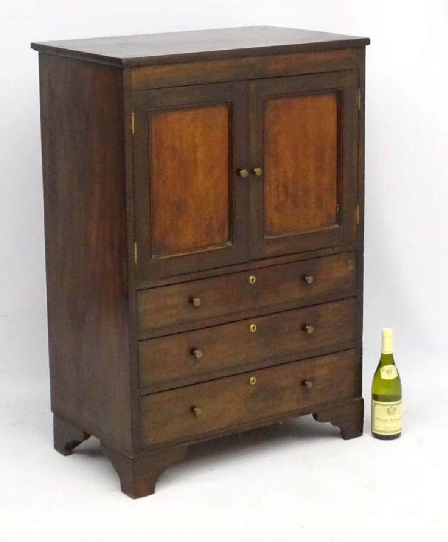 A Georgian mahogany drinks cabinet with cupboard over