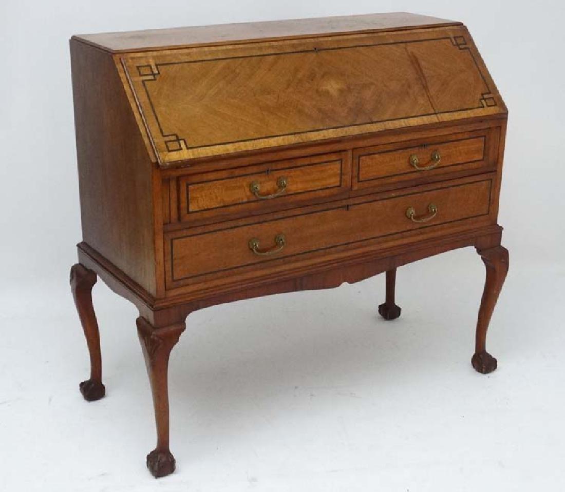 An early 20thC oak Bureau with ebony inlay, two long