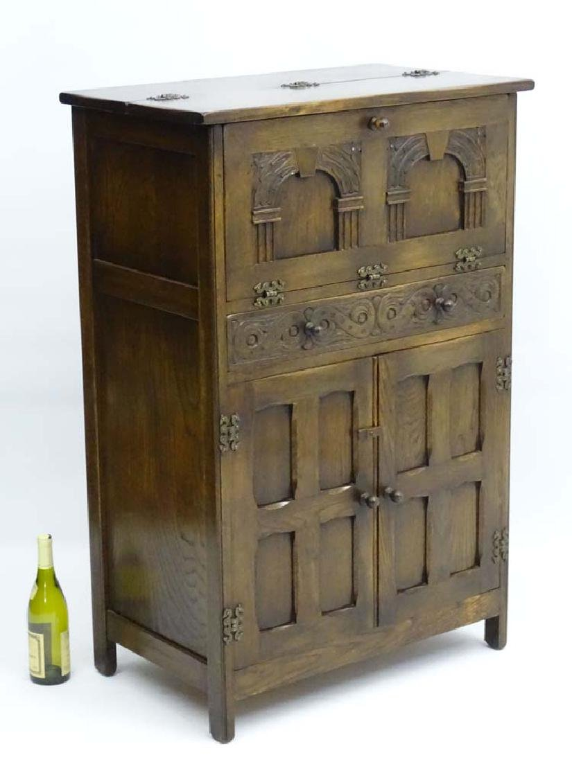 A mid 20thC drinks cabinet with Gothic carving to the