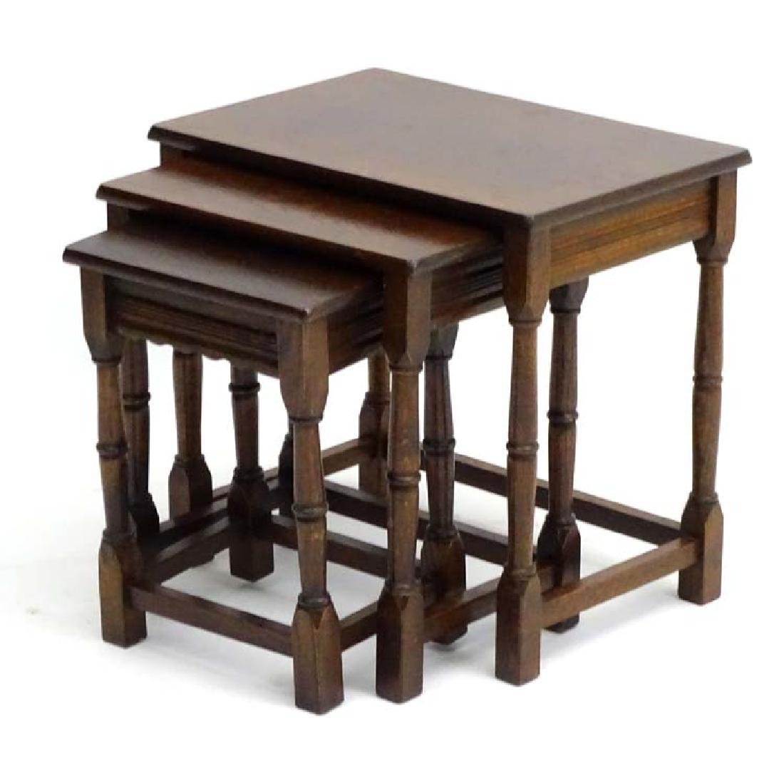 A 20thC nest of three oak tables with reeded decoration