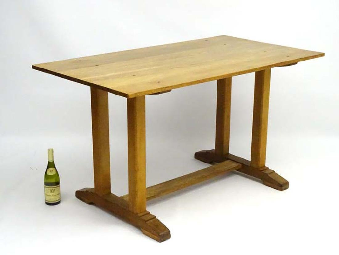 A mid 20thC oak trestle kitchen table in the manner of