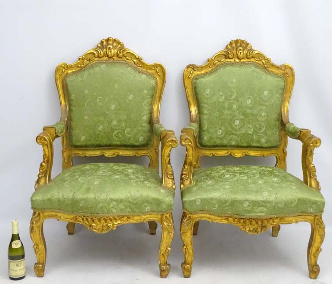 A pair of early 20thC gilt Italian open arm chairs