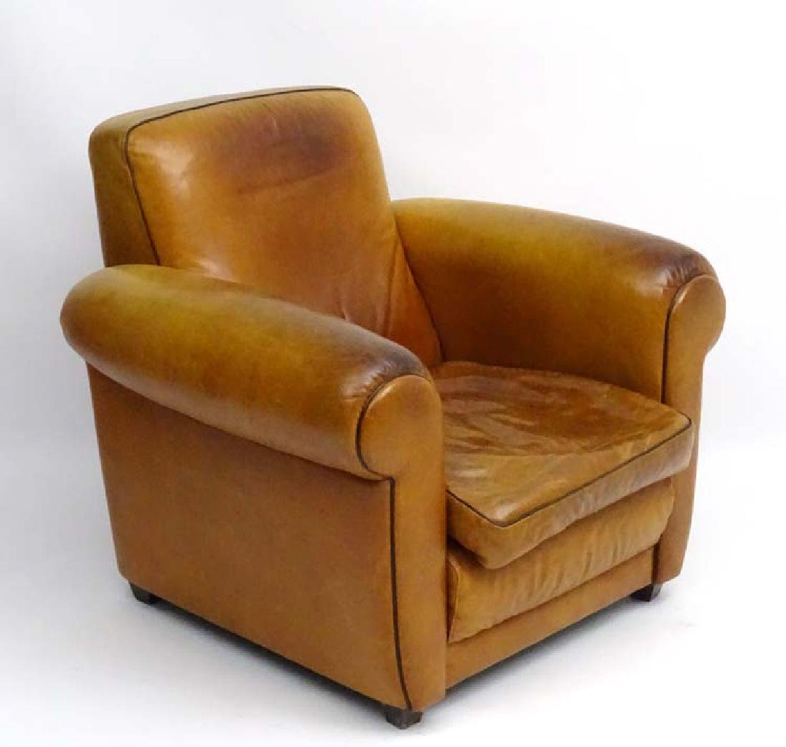 An Art Deco tan leather upholstered club armchair with