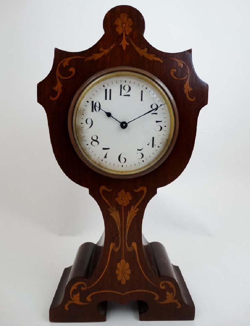 Art Nouveau inlaid and shaped clock, a key wind inlaid
