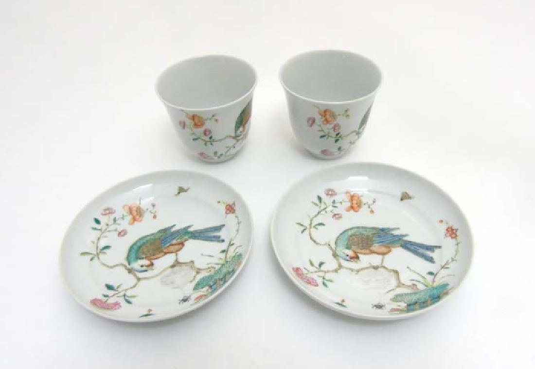 A pair of Chinese Famille Rose tea cups and saucers,