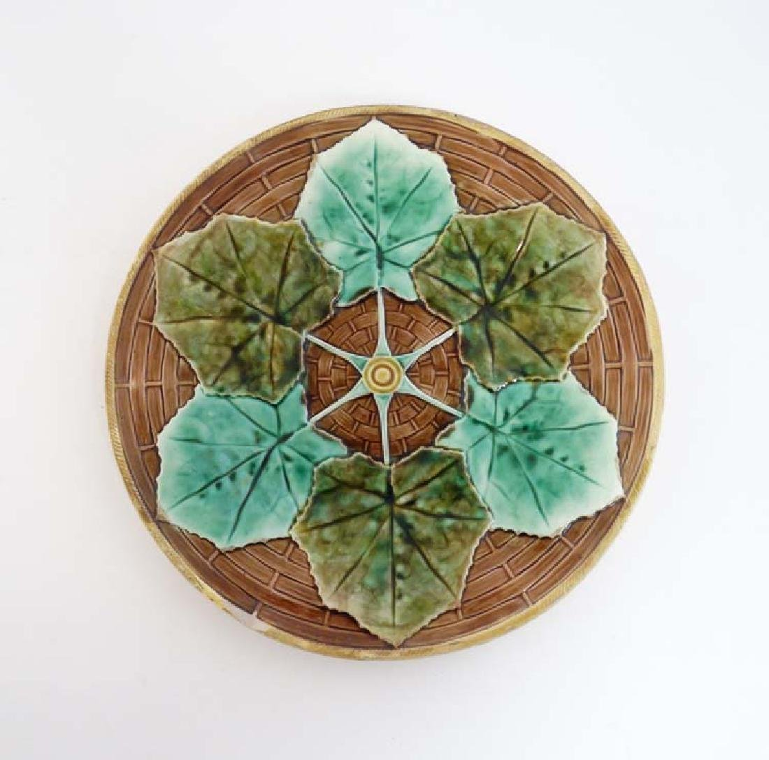 A 20th C majolica plate with 6 green leaf decoration,