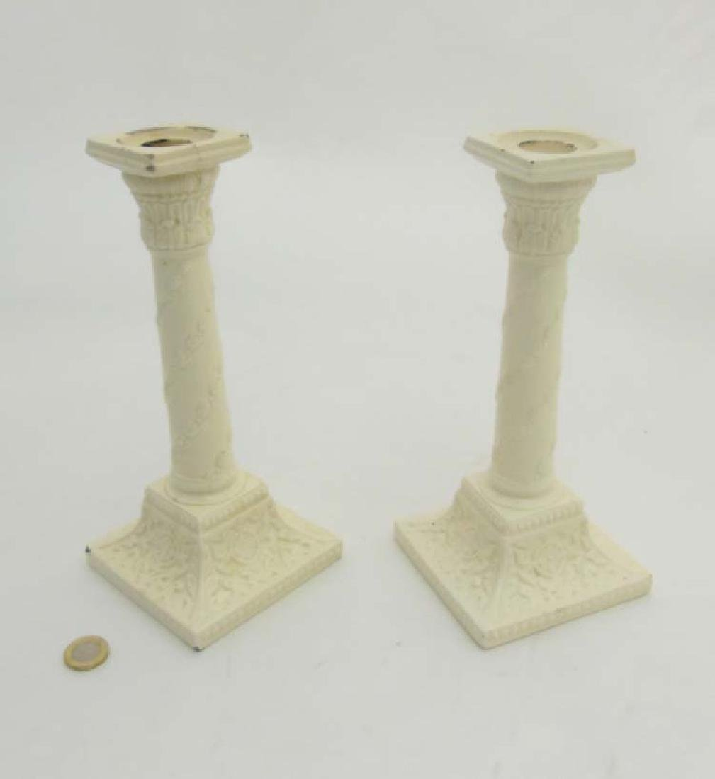 A pair of 20thC ceramic Creamware candlesticks in the