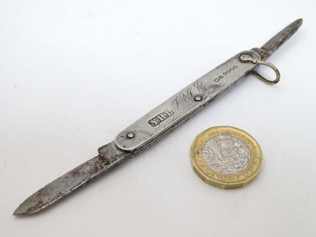 A silver handled folding fruit knife with 2 blades.