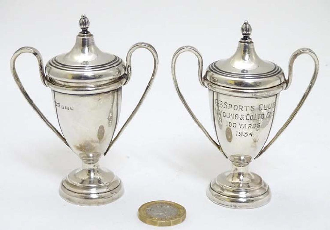 A pair of miniature twin handled trophy cups and covers