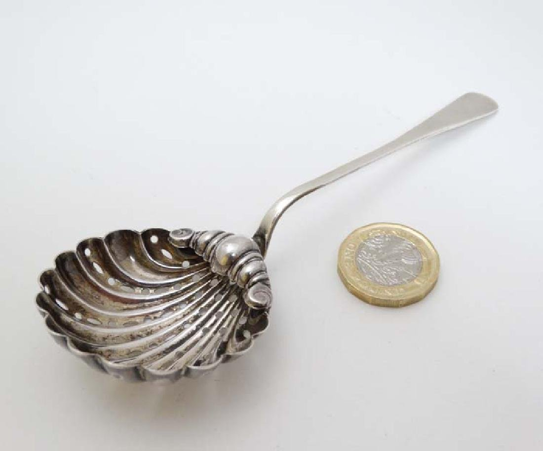 A silver sifter spoon with scallop shell formed bowl,
