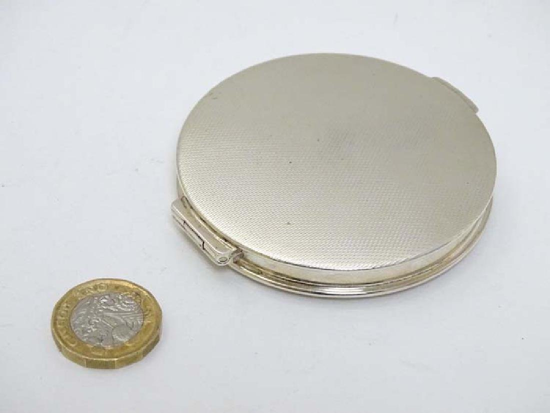 A silver compact of circular form with engine turned