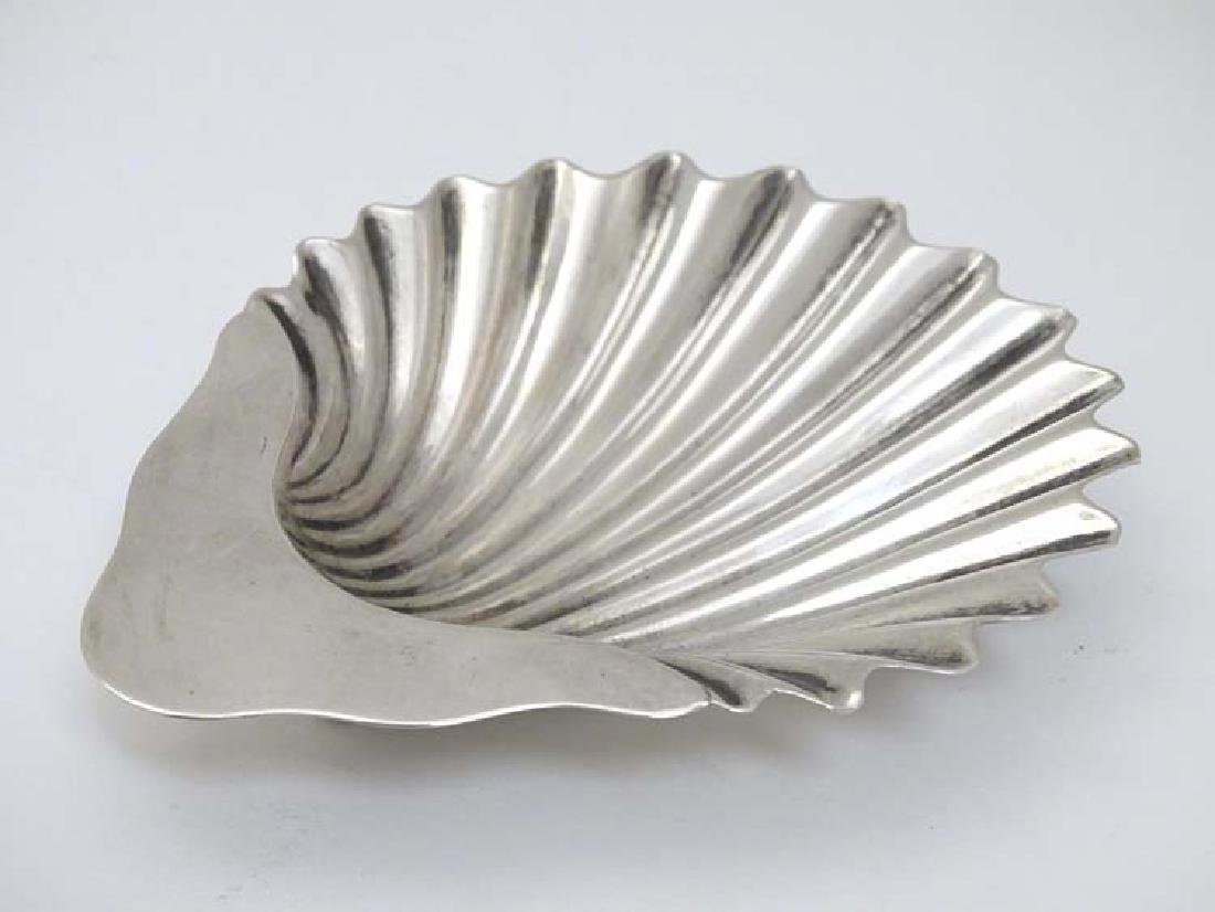 A silver shell formed butter dish on three ball feet.