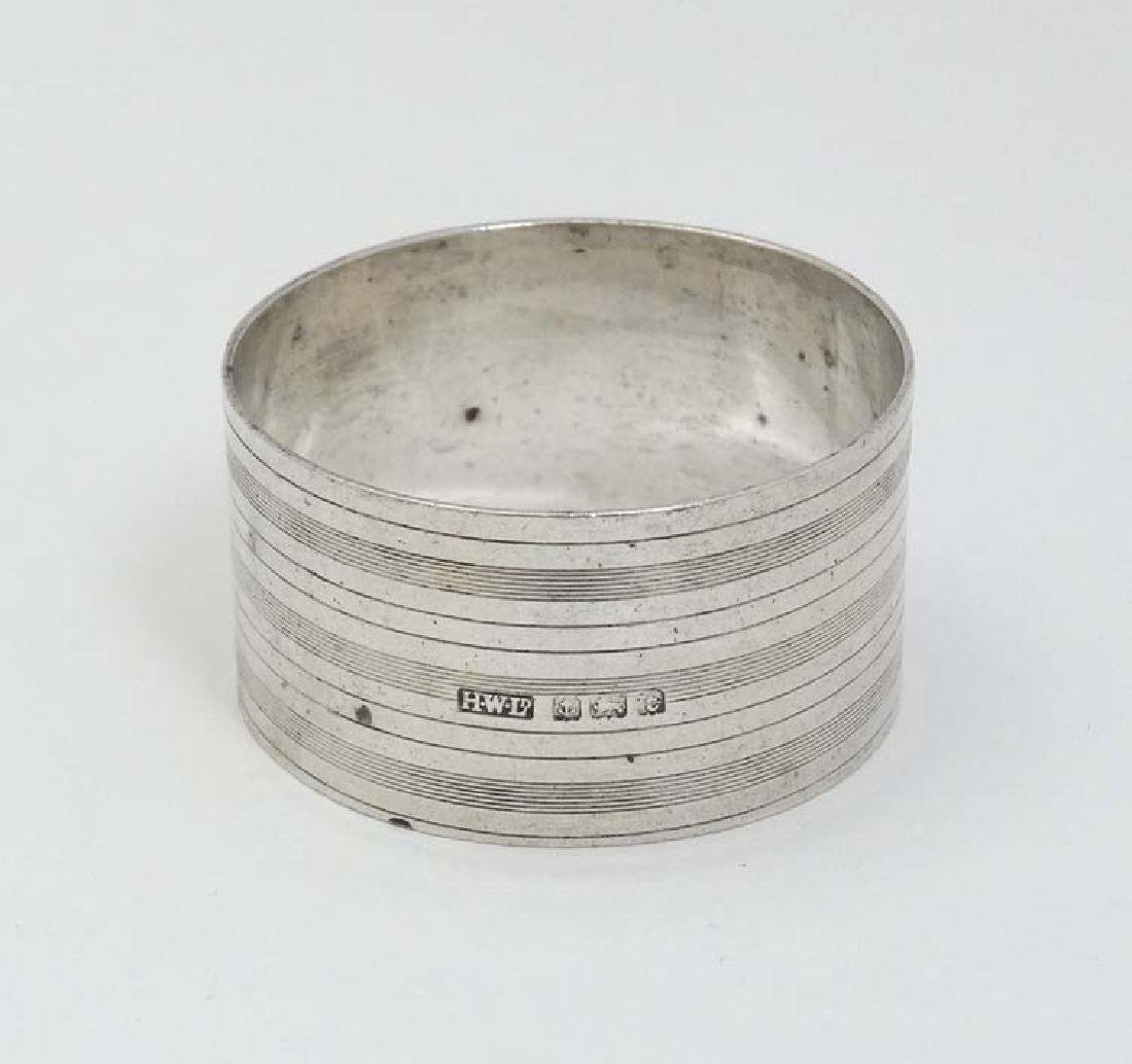 A silver napkin ring with banded engine turned
