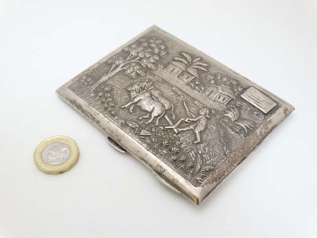 A silver cigarette case having cast decoration to lid