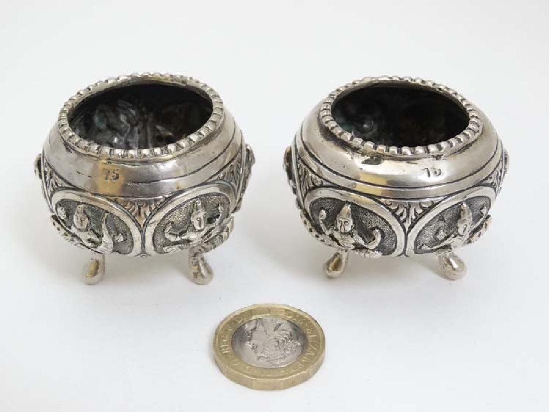 A pair of white metal salts with figural decoration.