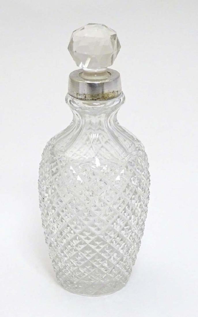 A cut glass scent / perfume bottle with silver plate