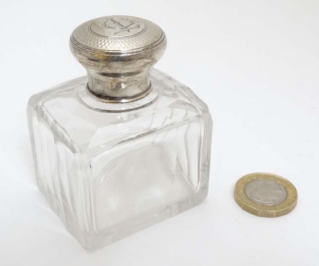A glass perfume / scent bottle with French silver top