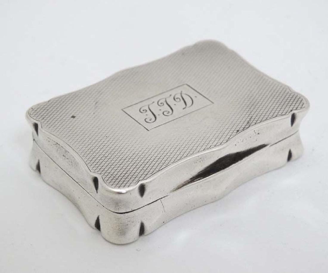 A silver snuff box with engine turned decoration.