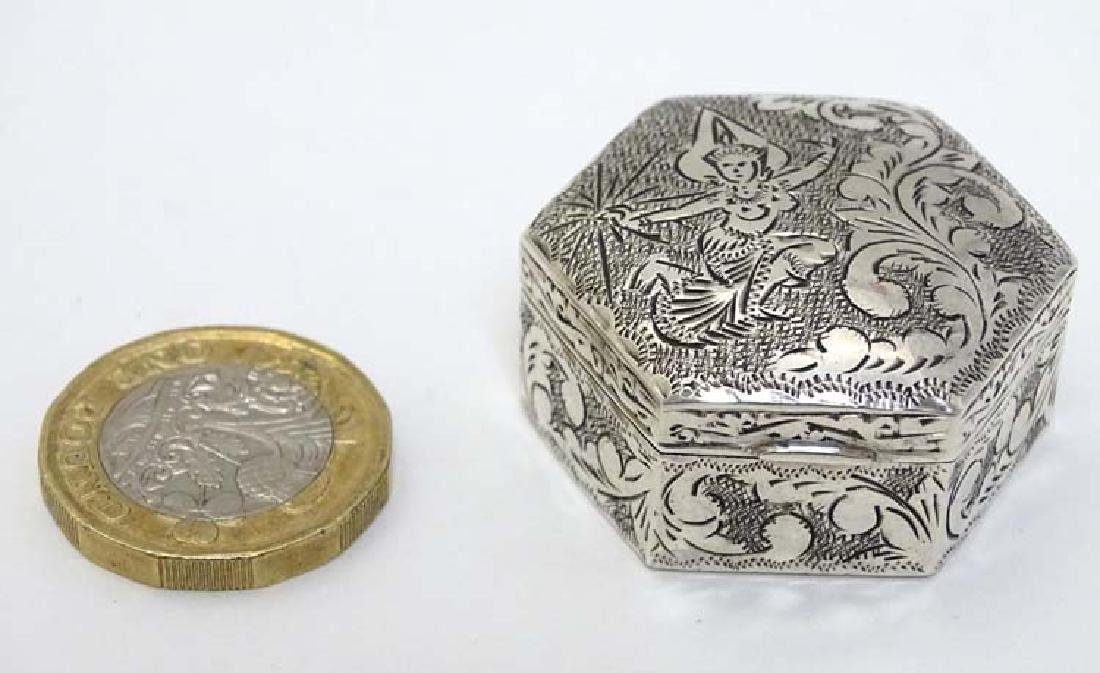 A silver pill box of hexagonal form with engraved