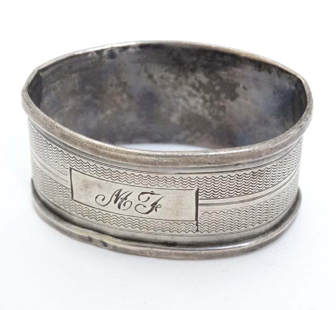 A silver napkin ring with engine turned decoration.