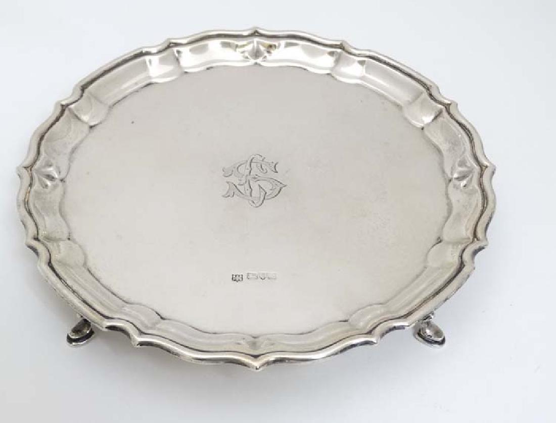 A silver visiting card tray / salver on four feet