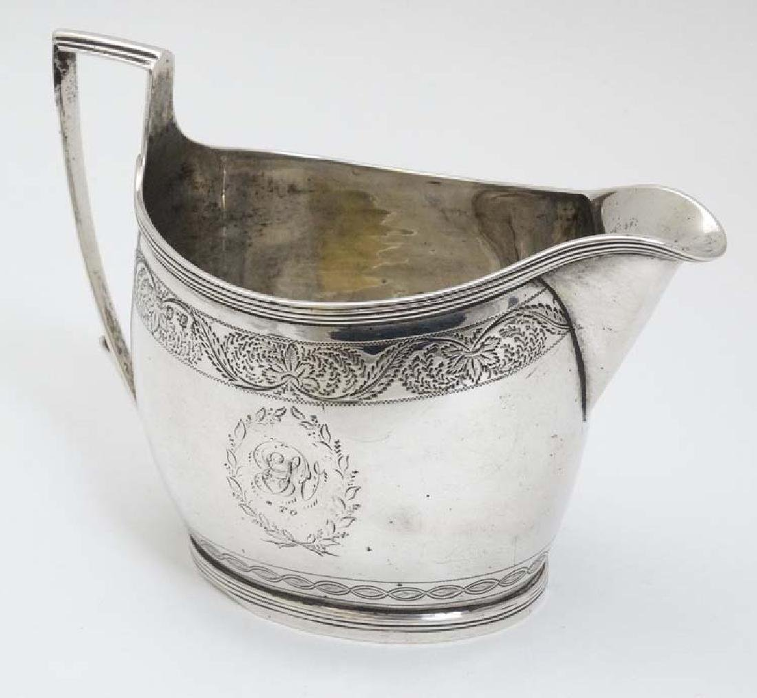 A Geo III silver cream jug  with engraved decoration