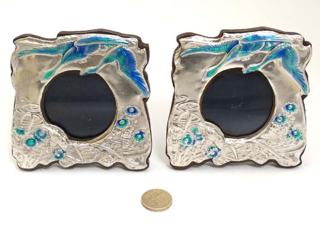 A pair of silver photograph frames with enamel floral