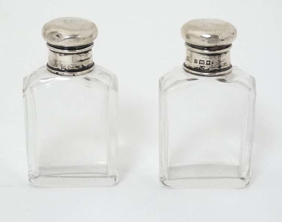 A pair of glass bottles with silver tops hallmarked
