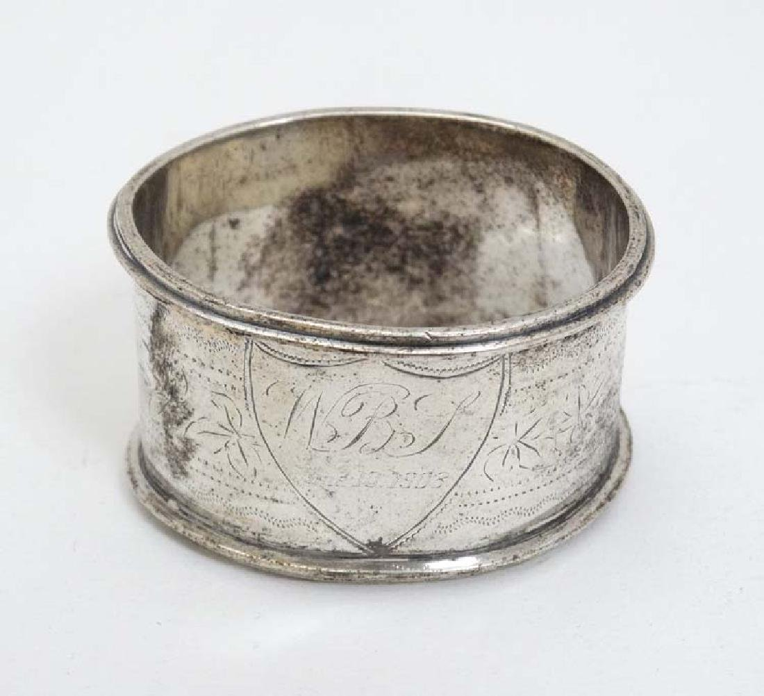 A silver napkin ring with engraved decoration.