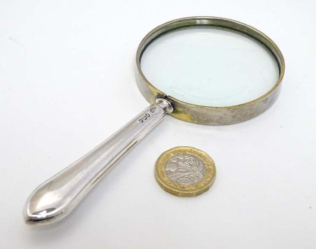 A magnifying glass with silver handle 5 1/2'' long