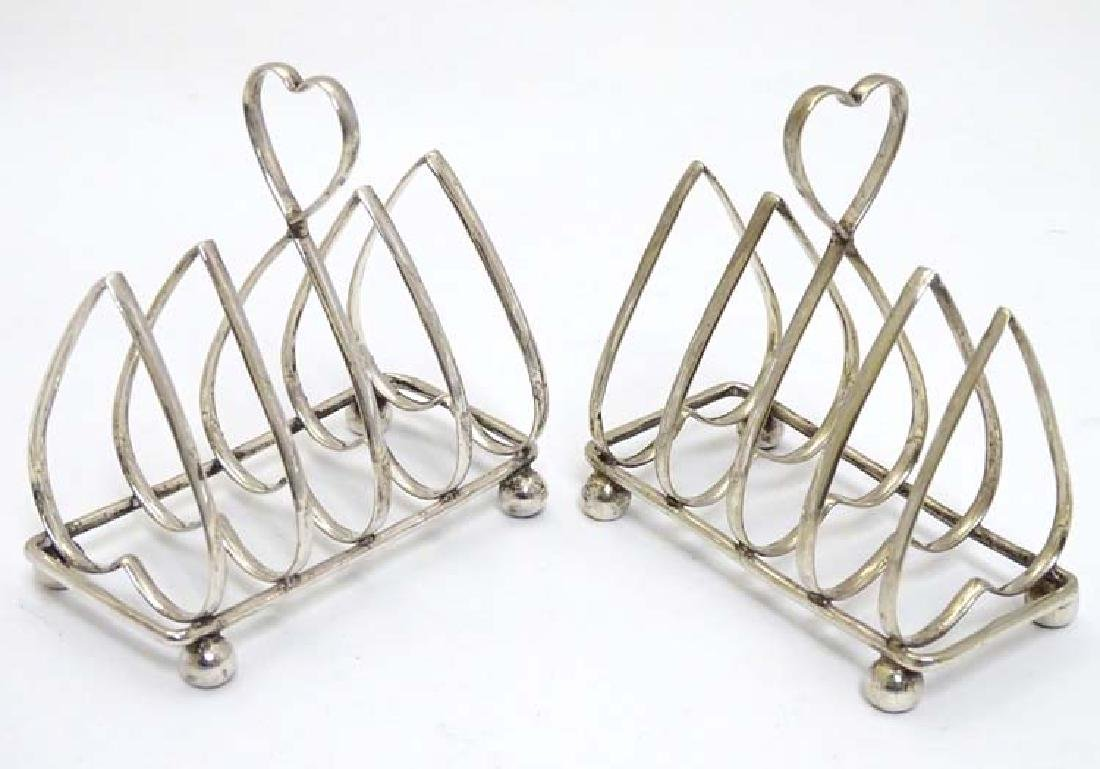 A pair of silver 4-slice toast rack with heart shaped