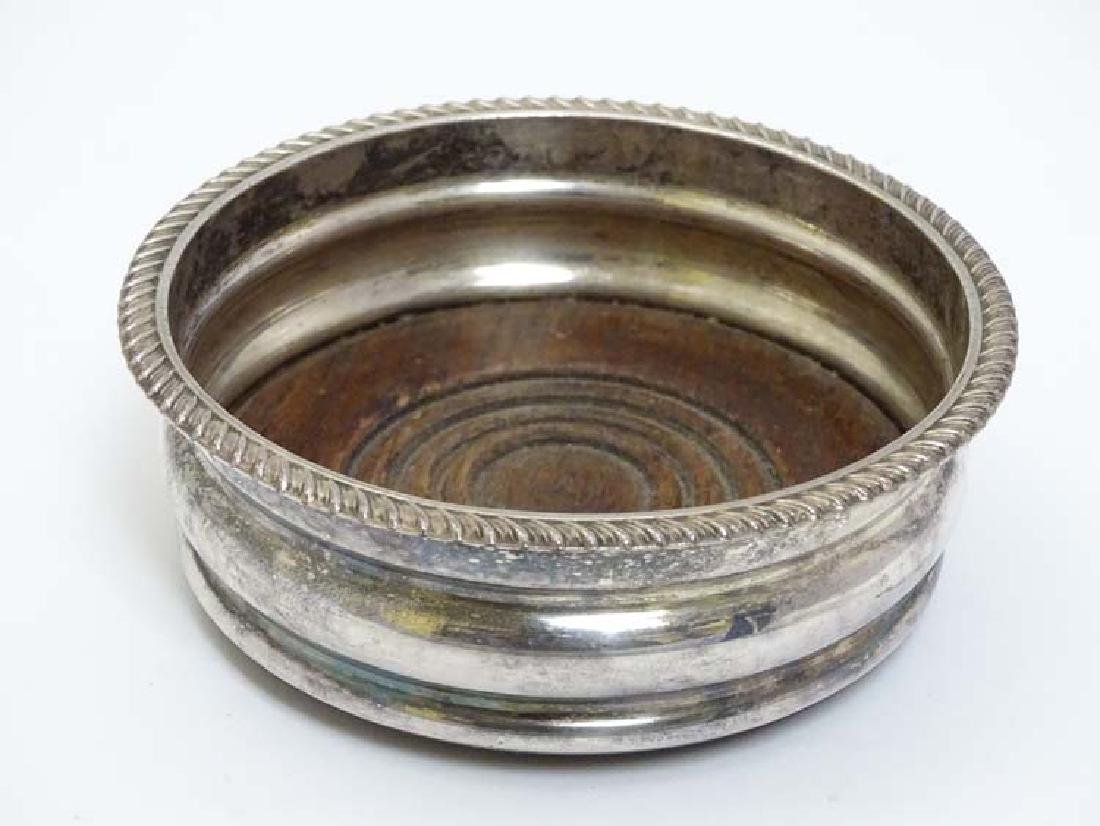 A silver plate coaster with gadrooned rim and turned
